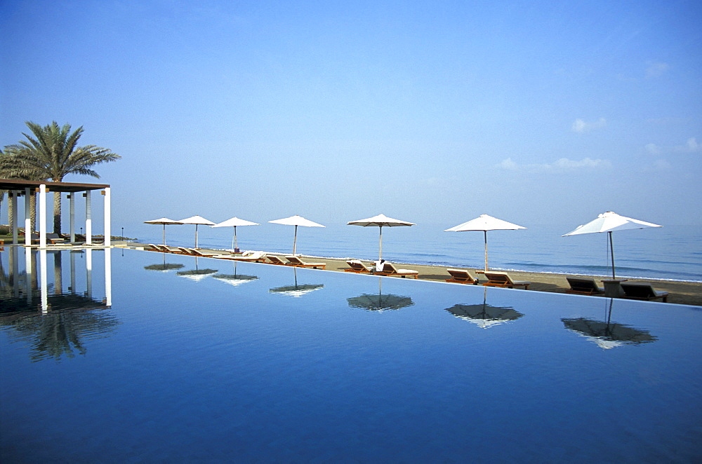 The pool reflecting sunshades, The Chedi Hotel, Muscat, Oman