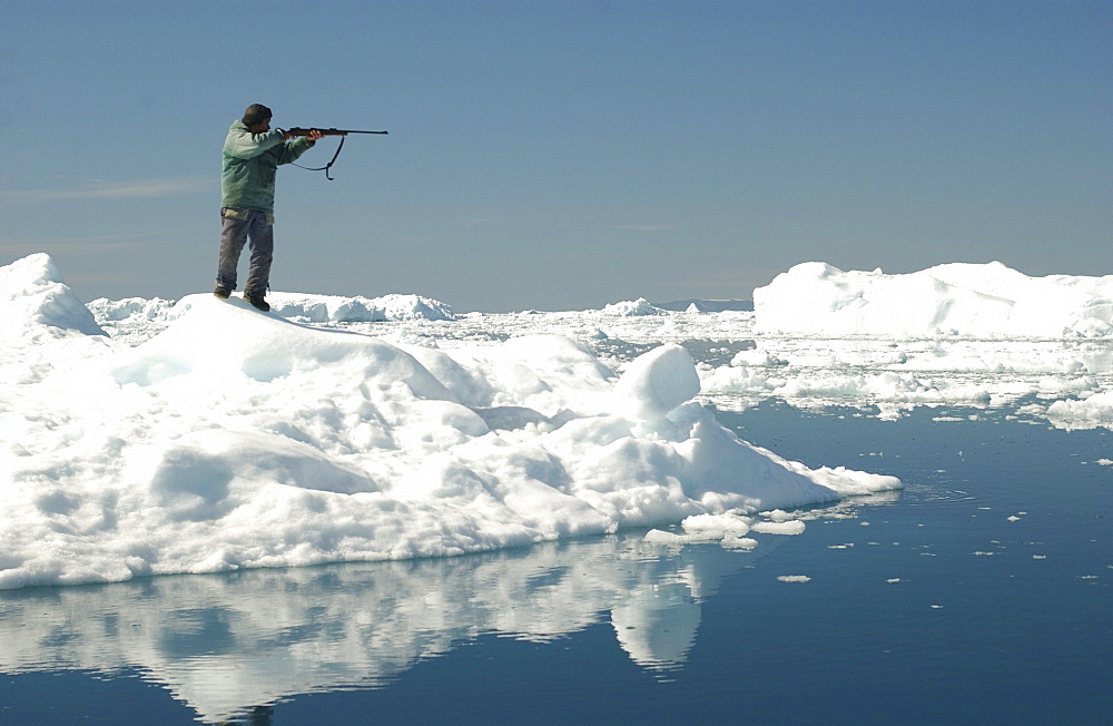 Hunter with rifle standing on the waterfront, Ilulissat, Greenland