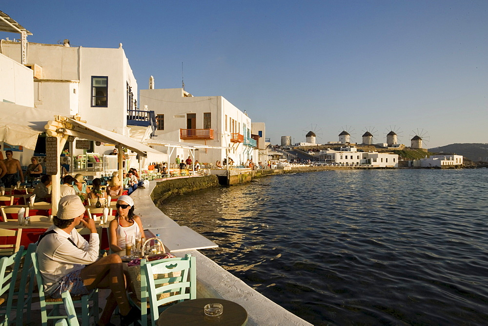 People sitting in restaurants and bars directly at sea, windmills in background, Little Venice, Mykonos-Town, Mykonos, Greece