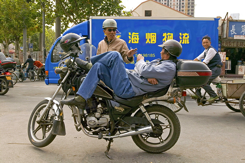 Traffic Shanghai, motorbike taxi, driver, courier, relaxed, lunch break, helmet, street junction