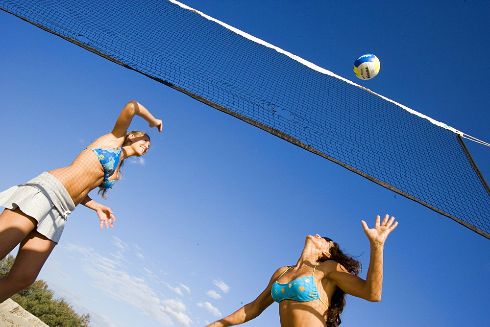 Two young woman playing beach volleyball, Apulia, Italy