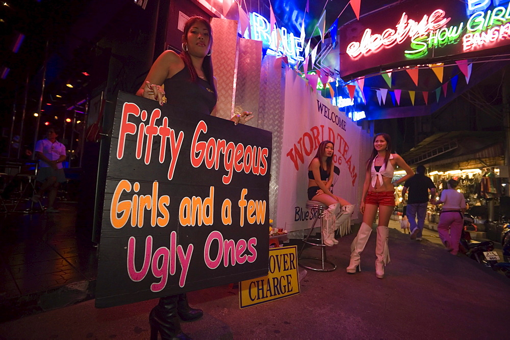 Three Go-go girls in front of a nightclub, one woman holding a sign, Patpong, red light and entertainment district, Bang Rak district, Bangkok, Thailand
