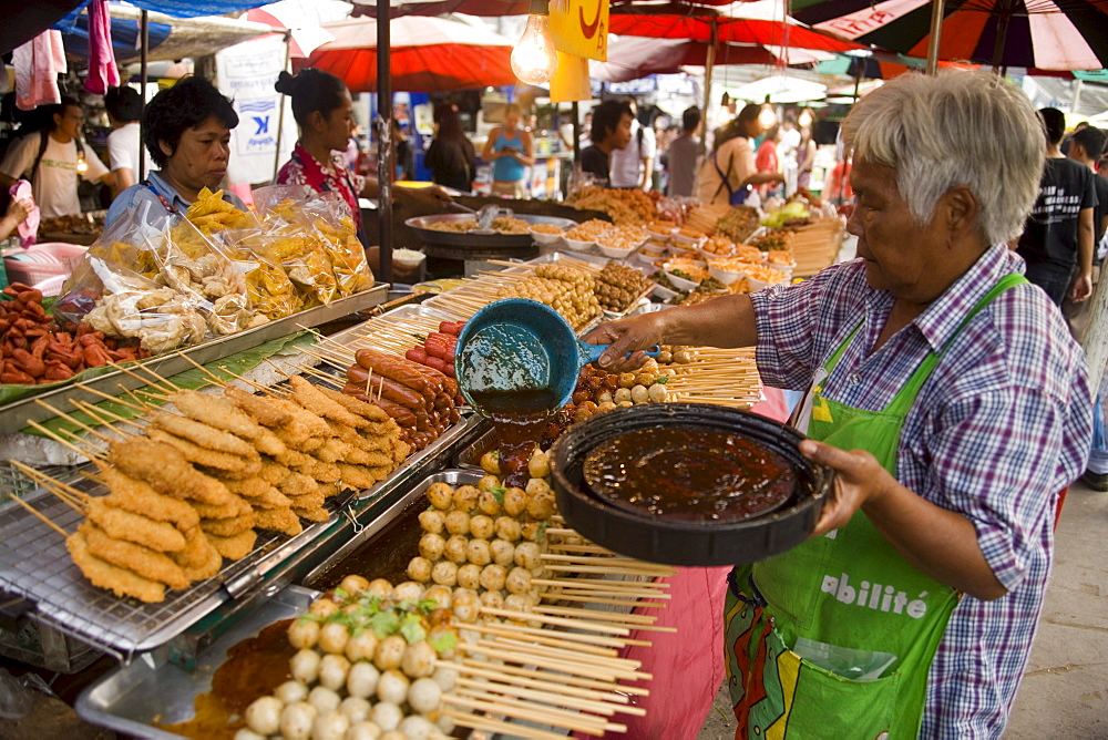 Woman preparing Thai food at Suan Chatuchak Weekend Market, Bangkok, Thailand