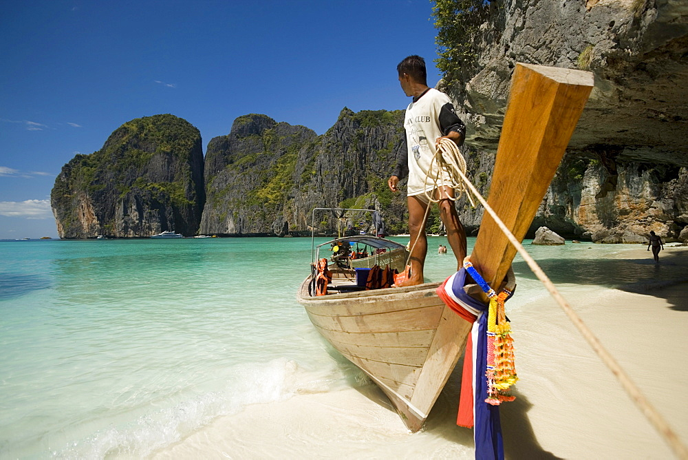 "Boatman standing on a long tail boat and holding a rope, Maya Bay, a beautiful scenic lagoon, famous for the Hollywood film ""The Beach"", Ko Phi-Phi Leh, Ko Phi-Phi Islands, Krabi, Thailand, after the tsunami"