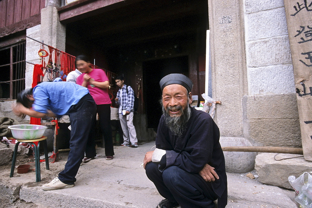 Abbot sitting in front of monastery and hostel Cui Yun Gong, Hua Shan, Shaanxi province, China, Asia