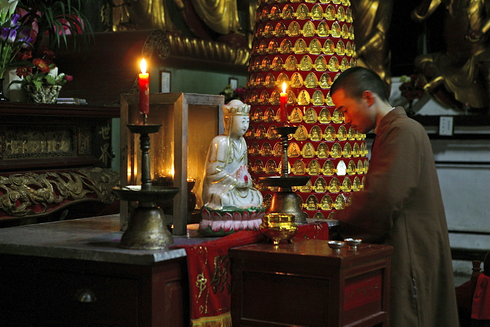 A monk kneeling in front of white Jade Buddha, Sangchan Monastery, Jiuhuashan, Anhui province, China, Asia