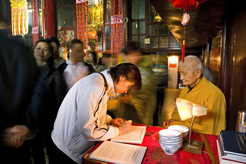 A monk and pilgrims at Longevity temple, Jiuhua Shan, Anhui province, China, Asia