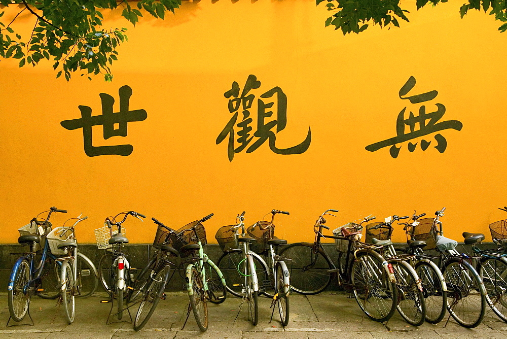 Yellow monastery wall with bicycles and calligraphy, Buddhist Island of Putuo Shan near Shanghai, East China Sea, China