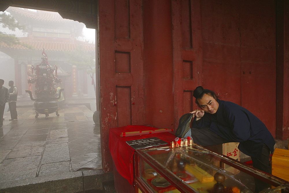 Taoist monk at the entrance to Bixia Si temple doing stretching exercises, Azure Clouds Temple, Mount Tai, Tai Shan, Shandong province, World Heritage, UNESCO, China