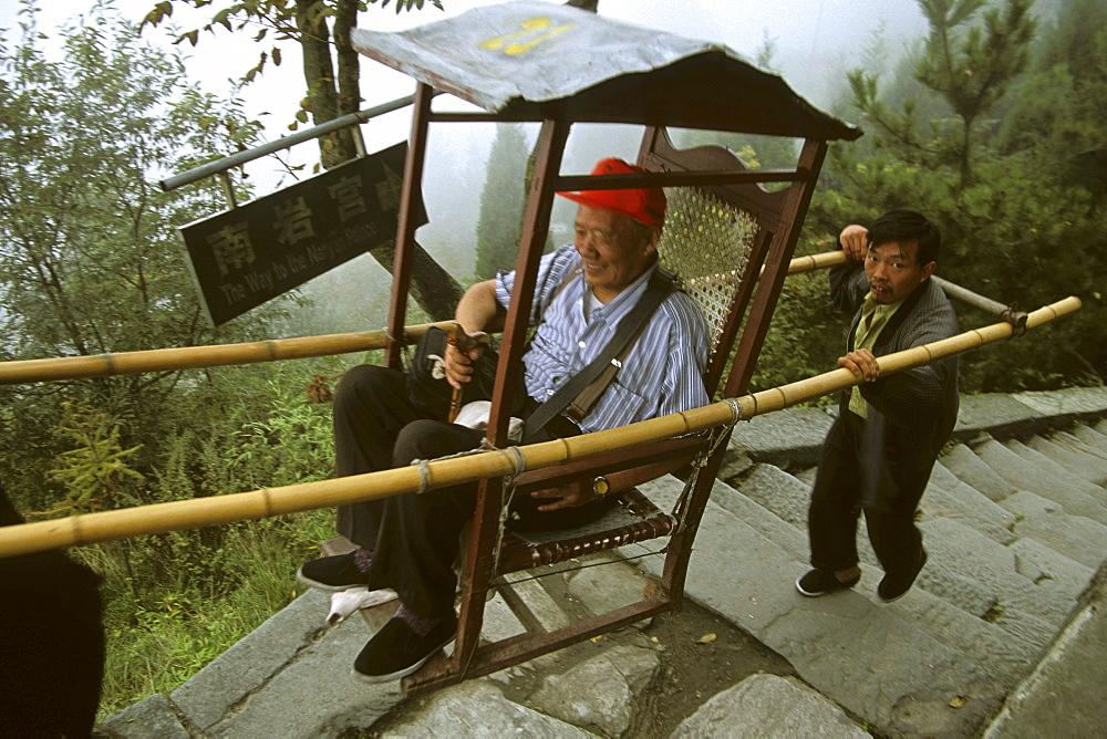 People carrying tourists in a litter, path to Nanya Palace, below the summit, 1613 metres high, Mount Wudang, Wudang Shan, Taoist mountain, Hubei province, UNESCO world cultural heritage site, birthplace of Tai chi, China