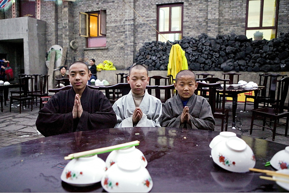 Young monks eating lunch, coal used cooking in the background, during birthday celebrations for Wenshu, Mount Wutai, Wutai Shan, Five Terrace Mountain, Buddhist Centre, town of Taihuai, Shanxi province, China