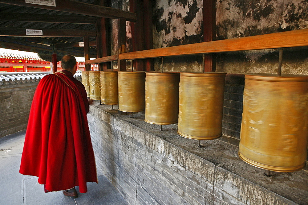 Lama monk turns the prayer wheels at the base of the Great White Pagoda, during the birthday celebrations for Wenshu, Tayuan Monastery, Wutai Shan, Five Terrace Mountain, Buddhist Centre, town of Taihuai, Shanxi province, China