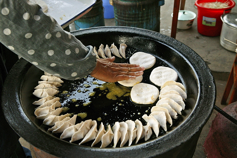 Jiaozi, cook turning fried Chinese ravioli, Chinese food, China