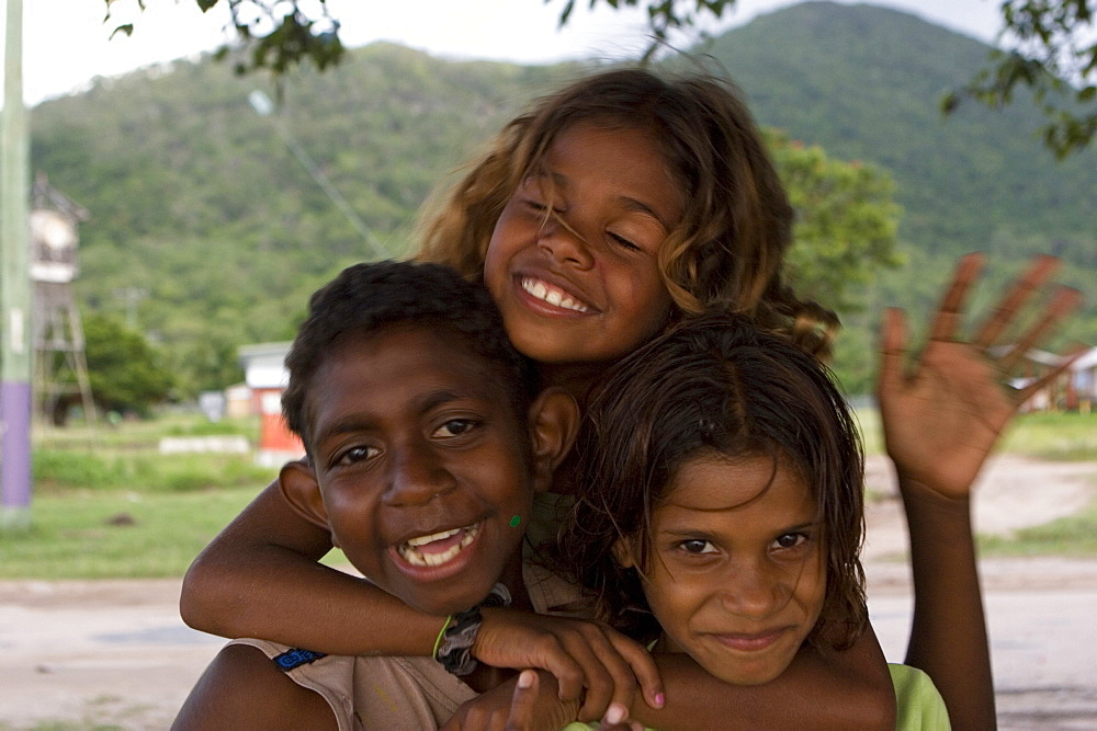 Portrait of three smiling Aborigine children at dusk, Palm Island, Queensland, Australia