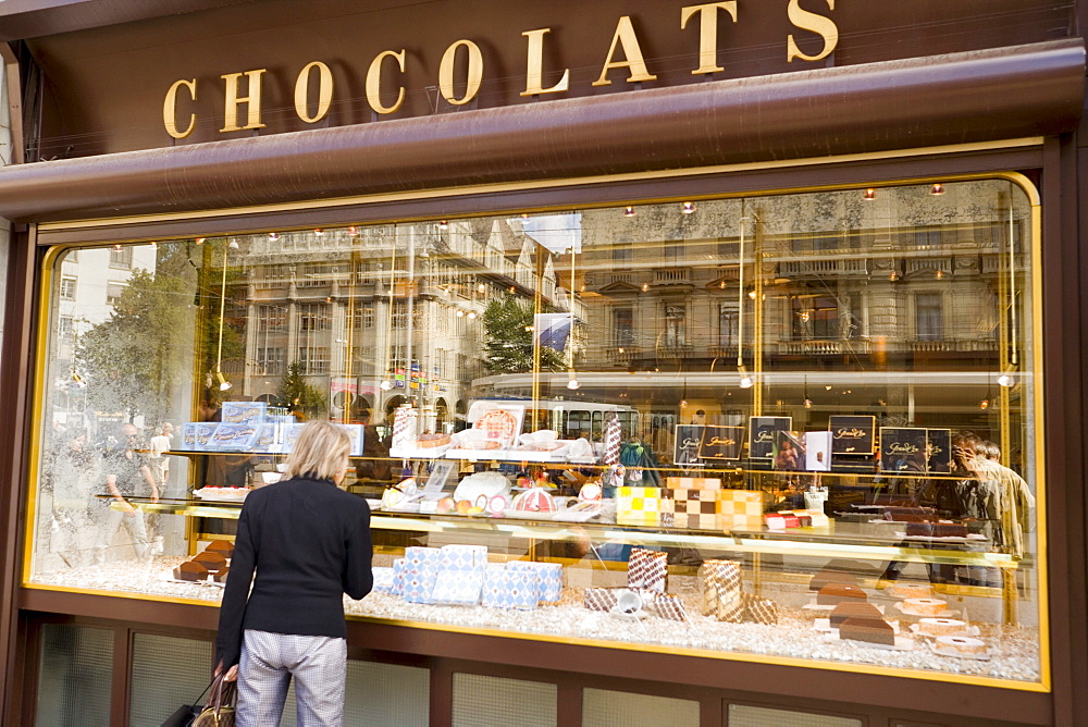 Woman standing at shop window of Spruengli (famous chocolate confectionery), Bahnhof Strasse, Zurich, Canton Zurich, Switzerland