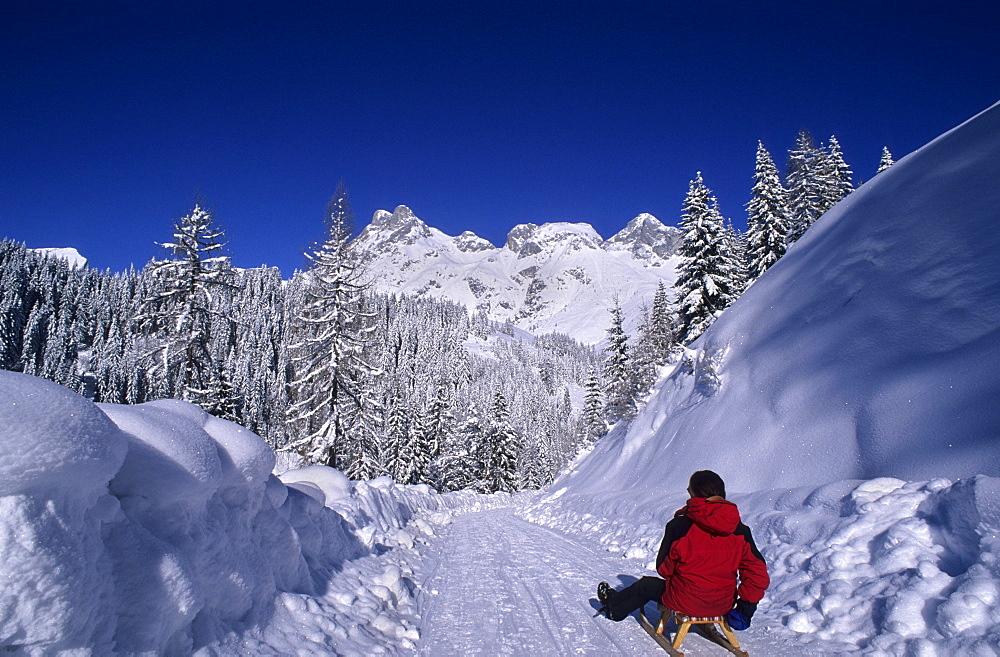 Person sledging on toboggan-run of Sportalm Strussing, view to Tennengebirge range, skiing area Werfenweng, Salzburg, Austria