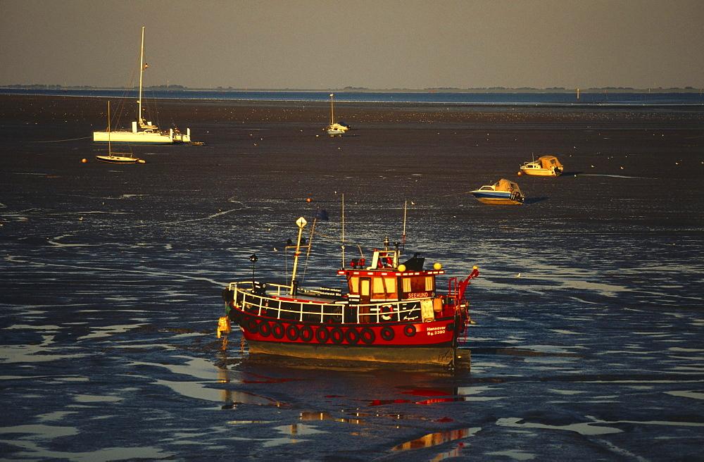 Boats on sandbanks at low tide, East Frisia, Germany