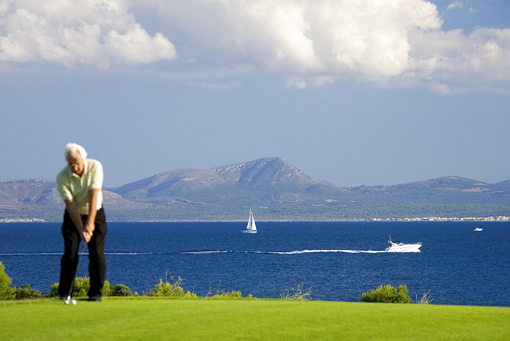 Senior man playing golf, Club de Golf Alcanada, Badia de Alcudia, Majorca, Spain