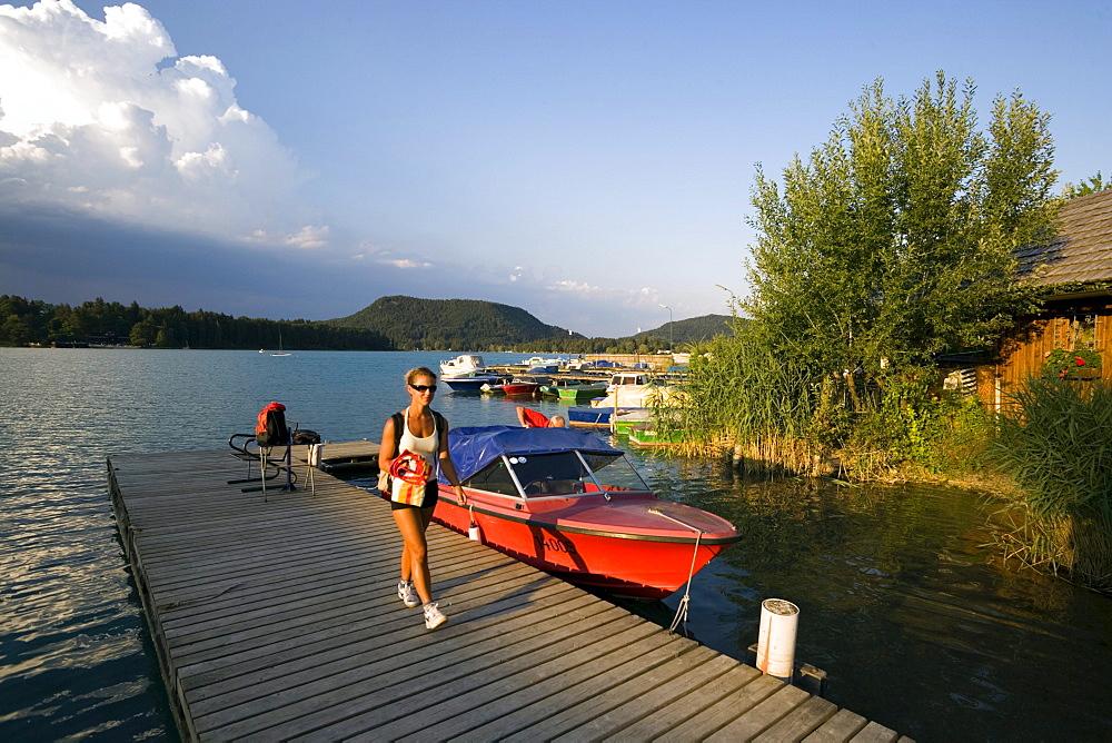 Woman walking over landing stage, Lake Faak, Carinthia, Austria