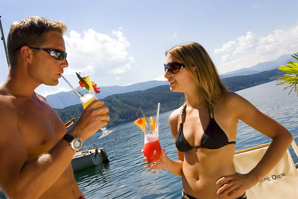 Couple wearing swimsuit and sunglasses drinking fruit cocktails, Millstaetter See (deepest lake of Carinthia), Millstatt, Carinthia, Austria