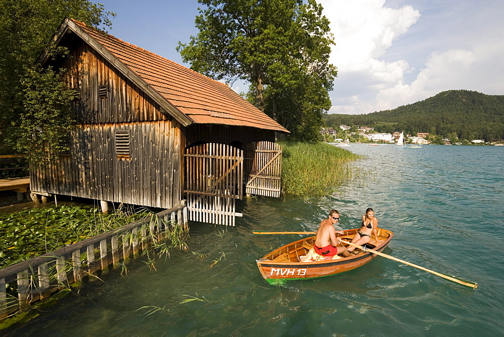 Young couple in a rowboat on Lake Faak near a boathouse, Carinthia, Austria