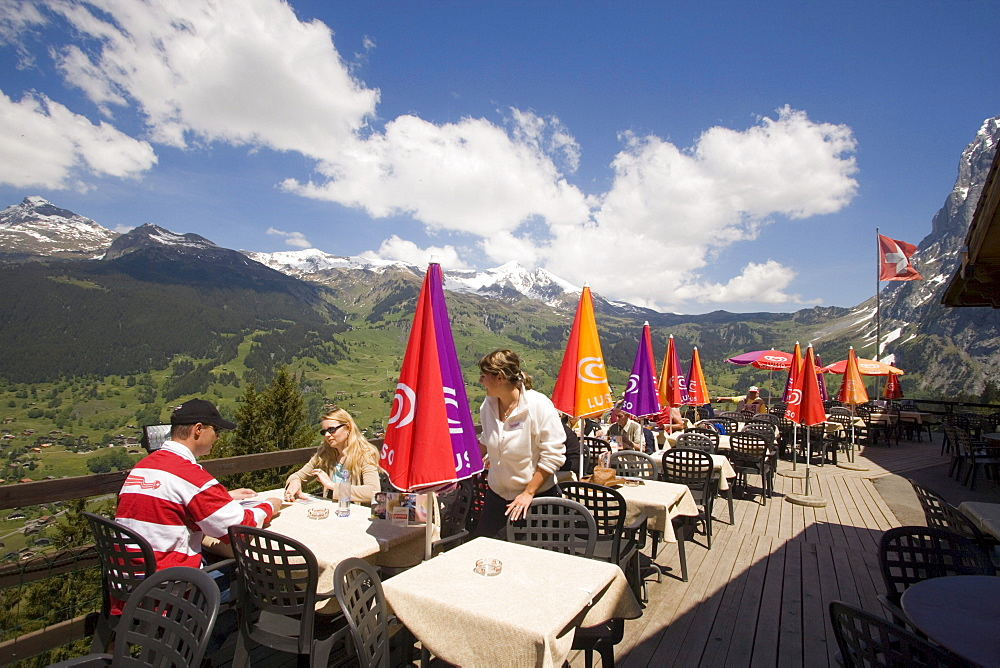 People on sun terrace of the mountain restaurant Pfingstegg, Schreckhorn (4078 m) and Eiger (3970 m) in background, Grindelwald, Bernese Oberland (highlands), Canton of Bern, Switzerland