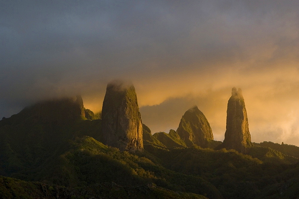 Mountain peaks of Ua Pou under cloud cover in the evening light, Marquesas, Polynesia, Oceania