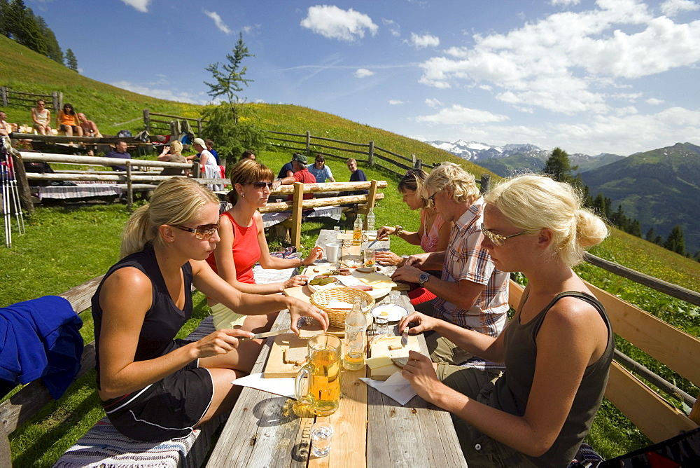 Tourists eating a Jause (snack) at Bichlalm (1731 m), Grossarl Valley, Salzburg, Austria