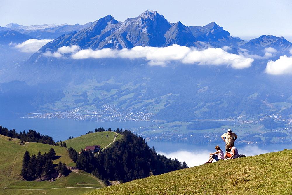 Three people on Rigi Kulm (1797 m) enjoying view over Lake Lucerne to Pilatus (2132 m), Rigi Kulm, Canton of Schwyz, Switzerland