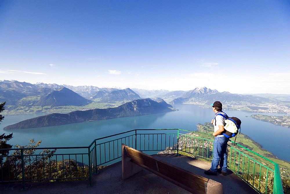 Man standing on vantage point Kaenzli, mount Rigi (1797 m, Queen of the Mountains) and looking over Lake Lucerne with Weggis, mount Buergenstock and mount Pilatus (2132 M), Rigi Kaltbad, Canton of Schwyz, Switzerland
