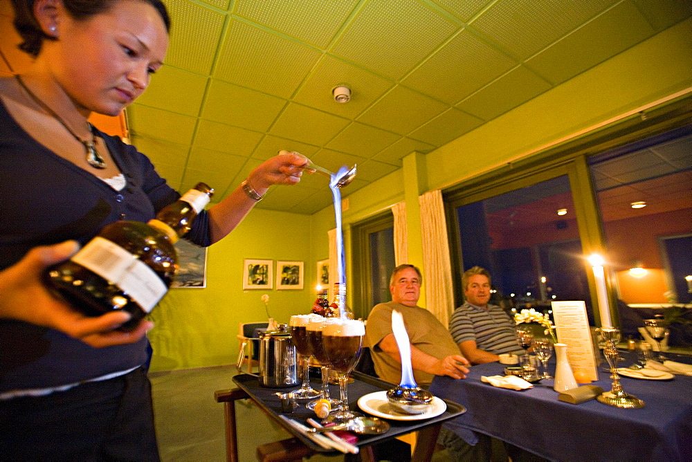 A waitress serves greenland coffee at Qaqortoq former Julianehab), the burning alcohol simbolizes the aurora borealis, the white cream the ice and the coffee the soil, South Greenland.