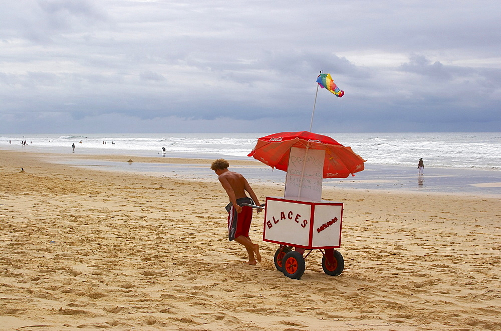 Young man selling ice-cream at the beach of Carcans Plage, dept Gironde, France, Europe