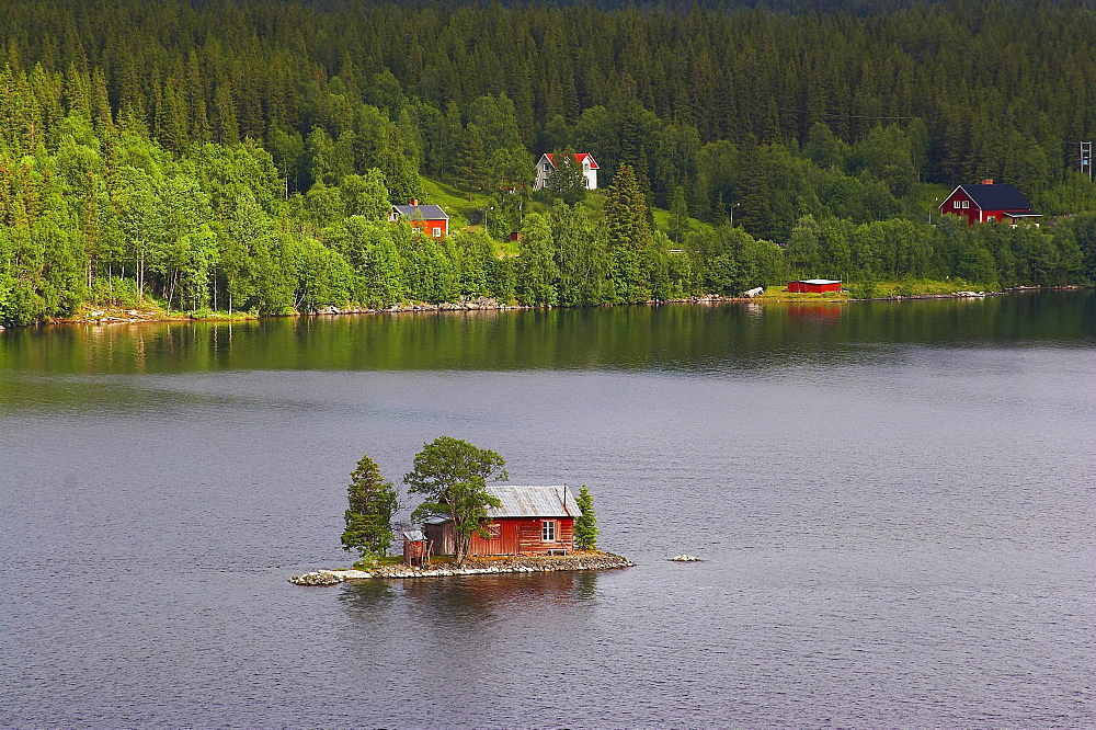 Small island with red wooden house in the lake Hetoegeln near Gaeddede, Jaemtland, northern Sweden