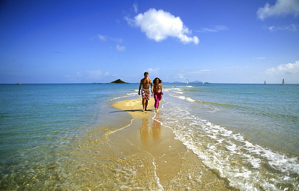 A couple walking along the beach, Sandy Point on Brampton Island, Whitsunday Islands, Great Barrier Reef, Australia