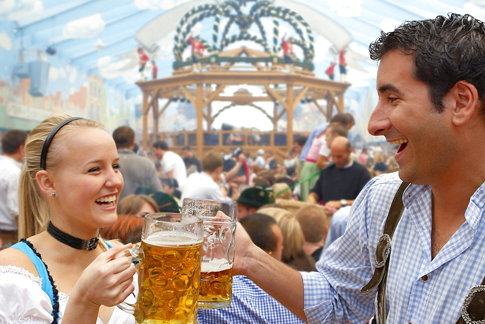 Young couple drinking beer during Oktoberfest, Munich, Bavaria, Germany