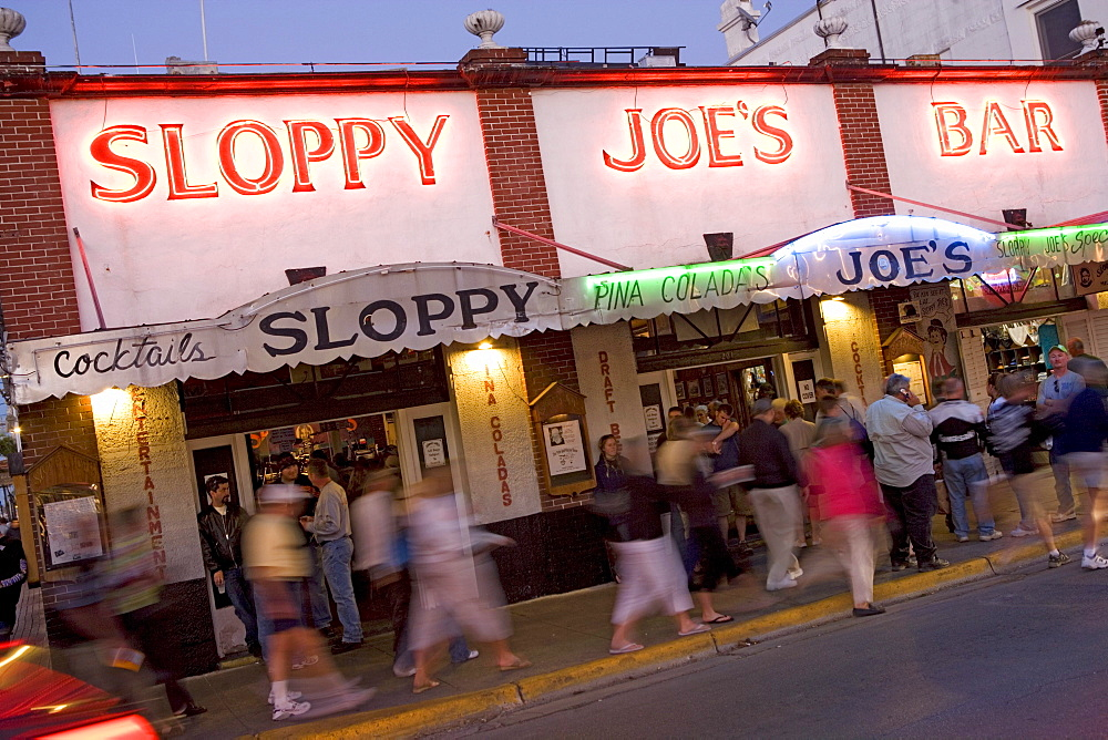 People standing in front of Sloopy Joes Bar in the evening, Duval Street, Key West, Florida Keys, Florida, USA