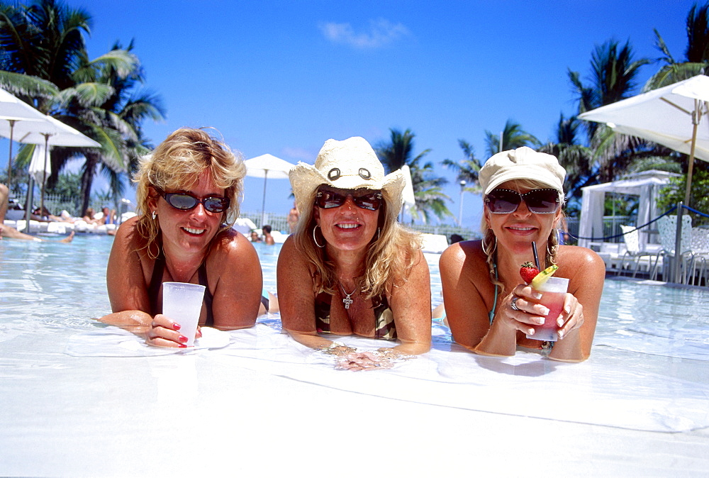 Girls with cocktails at swimming pool, South Beach, Miami, Florida, USA
