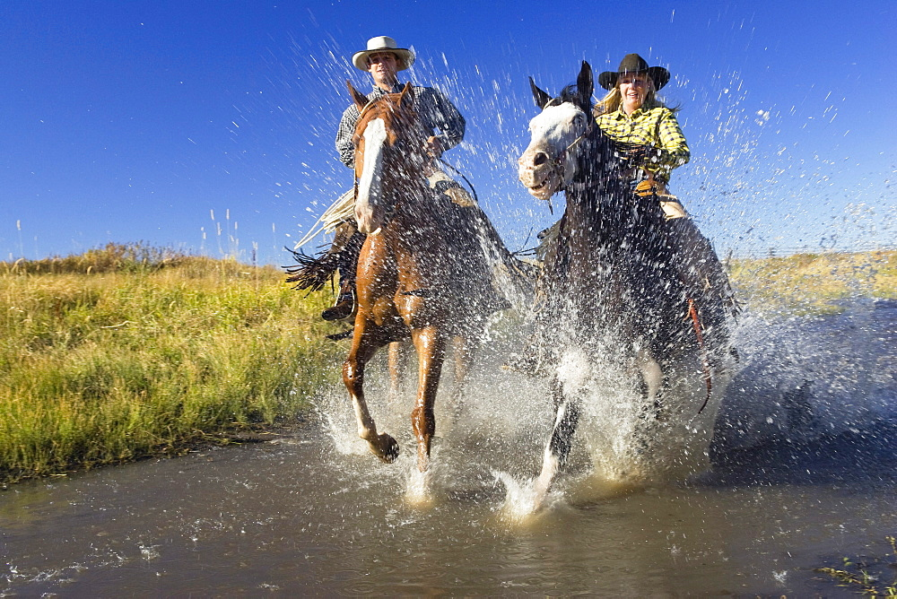 Cowboy and cowgirl riding through creek, wild west, Oregon, USA
