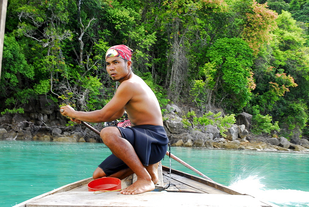 Local man steering a longtail boat, Surin Islands Marine National Park, Ko Surin, Phang Nga, Thailand