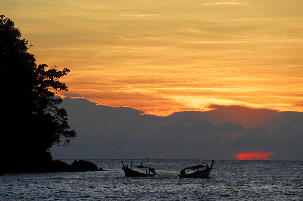 Two longtail boats at sunset from backside beach at Surin Islands Marine Natinal Park, headquarters, Ko Surin, Phang Nga, Thailand