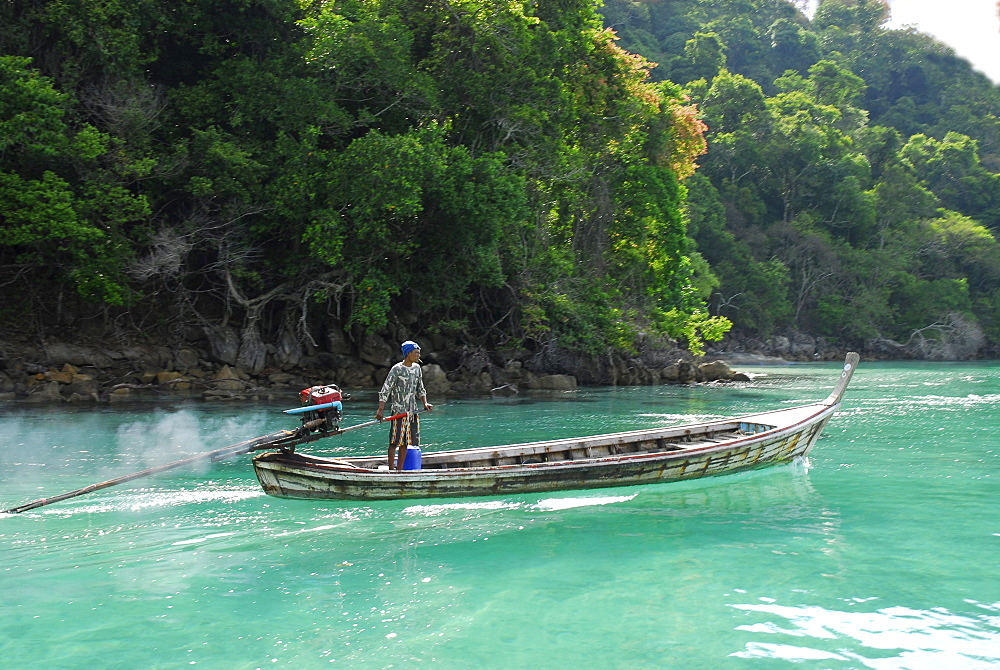 Longtail boat in front of jungle clad island, Surin Islands Marine National Park, Ko Surin, Phang Nga, Thailand
