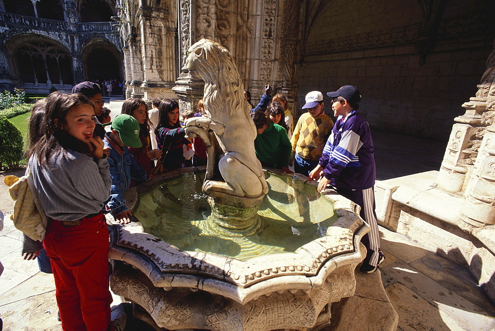 A group of children standing near a fountain, Cloister, Mosteiro dos Jeronimos, Hieronymites Monastery, Belem, Lisbon, Portugal