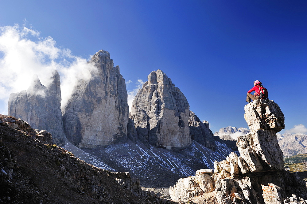 Woman sitting on a rock tower in front of the three peaks, Tre Cime di Lavaredo, Sexten Dolomites, Dolomites, UNESCO World Heritage Site, South Tyrol, Italy