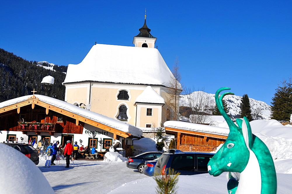 Mountain hut and church in the sunlight, Aschau, Kitzbuehel, Winter in Tyrol, Austria, Europe