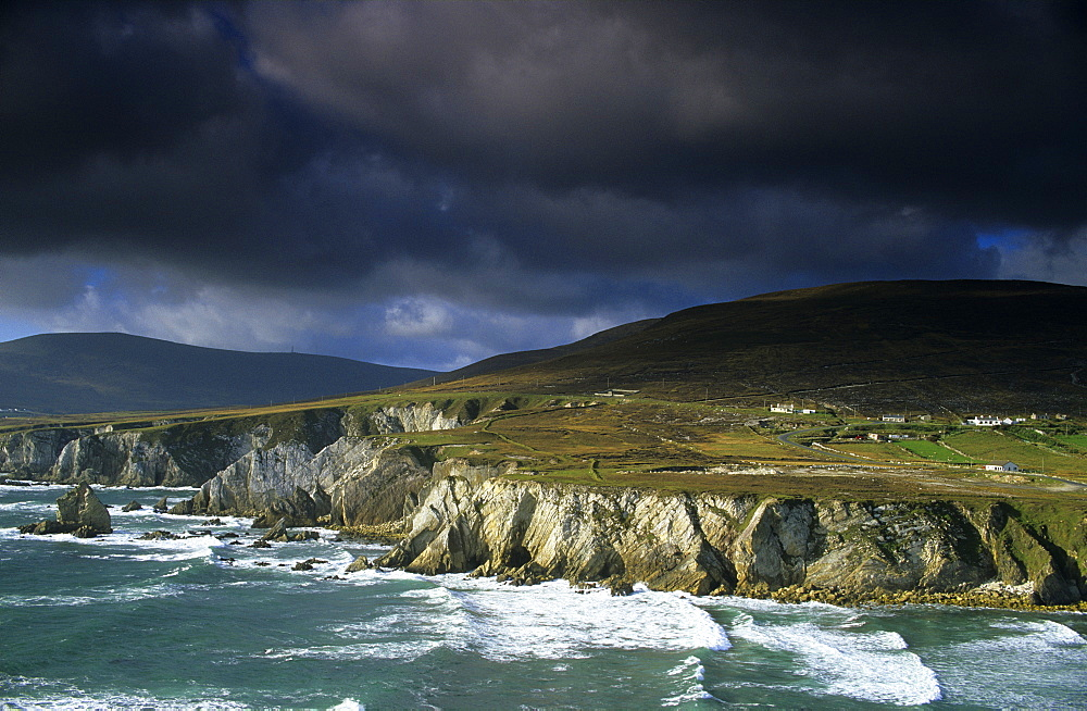 Surge in front of the steep coast under dark clouds, Achill Island, County Mayo, Ireland, Europe