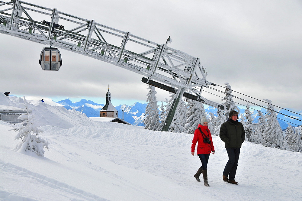 Man and woman in front of the cableway, on the Wallberg, winter in Bavaria, Mangfall Range, Bavarian Pre-Alps, Upper Bavaria, Bavaria, Germany
