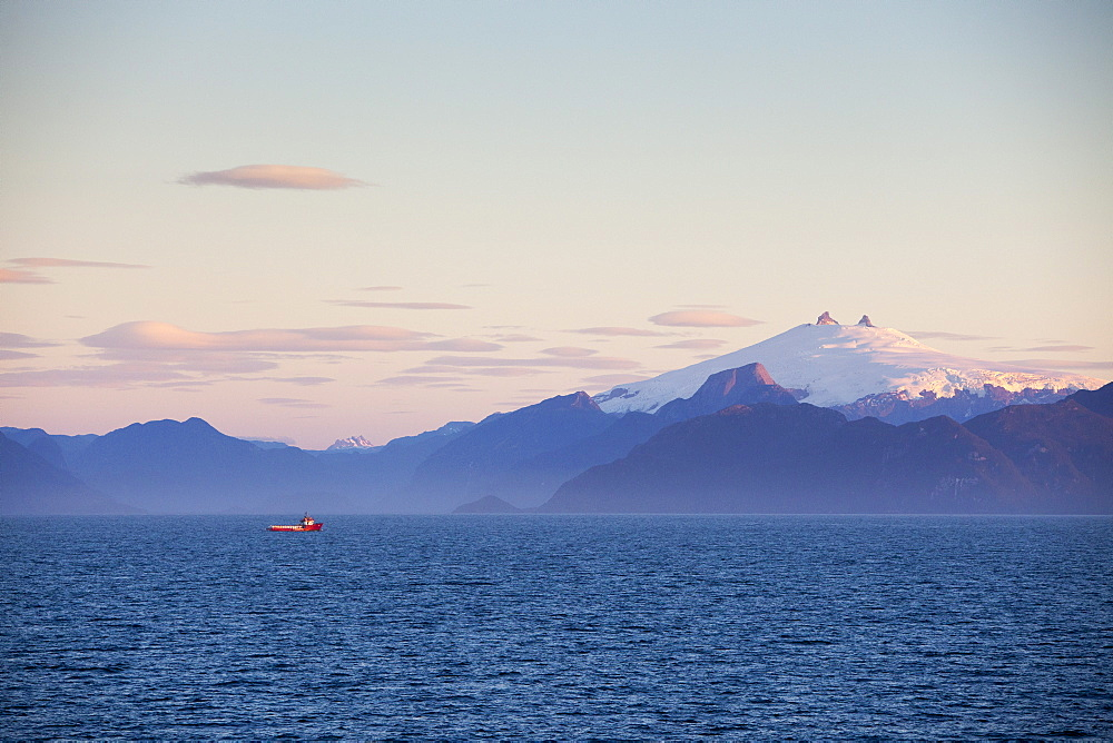 Fishing boat and snow-covered volcanic peak at sunset, Chilean fjords, Magallanes y de la Antartica Chilena, Patagonia, Chile, South America