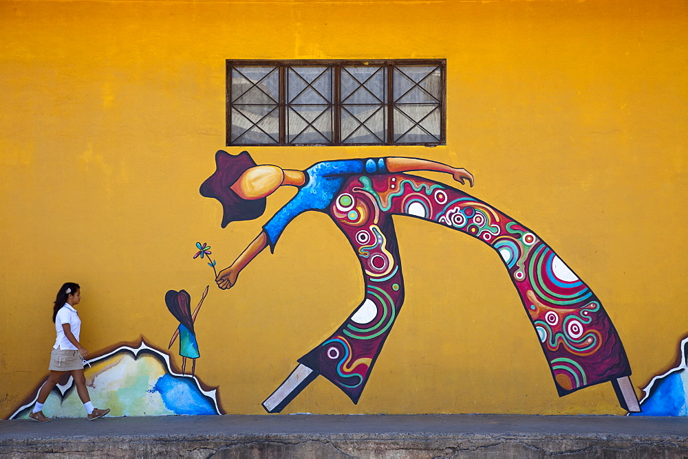 School girl walks in front of mural, Puntarenas, Costa Rica, Central America