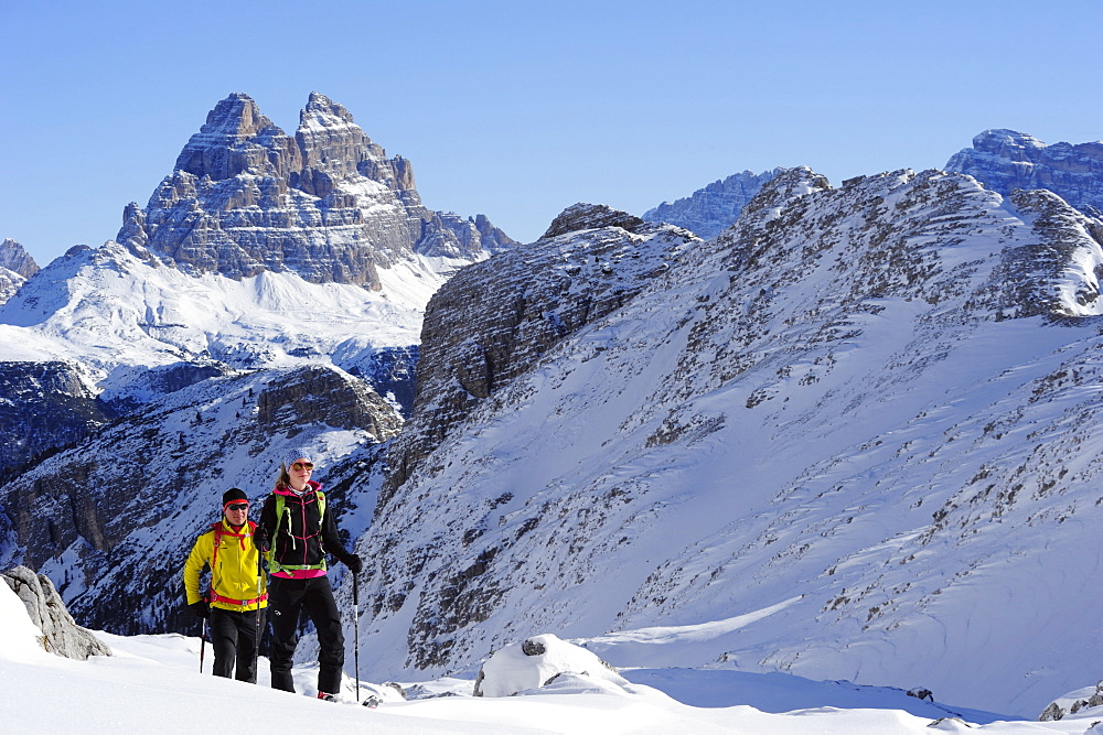 Young woman and young man ascending with crosscountry skis to Corno d'Angolo, Tre Cime di Lavaredo in background, Corno d'Angolo, Cortina, Veneto, Dolomites, Italy, Europe