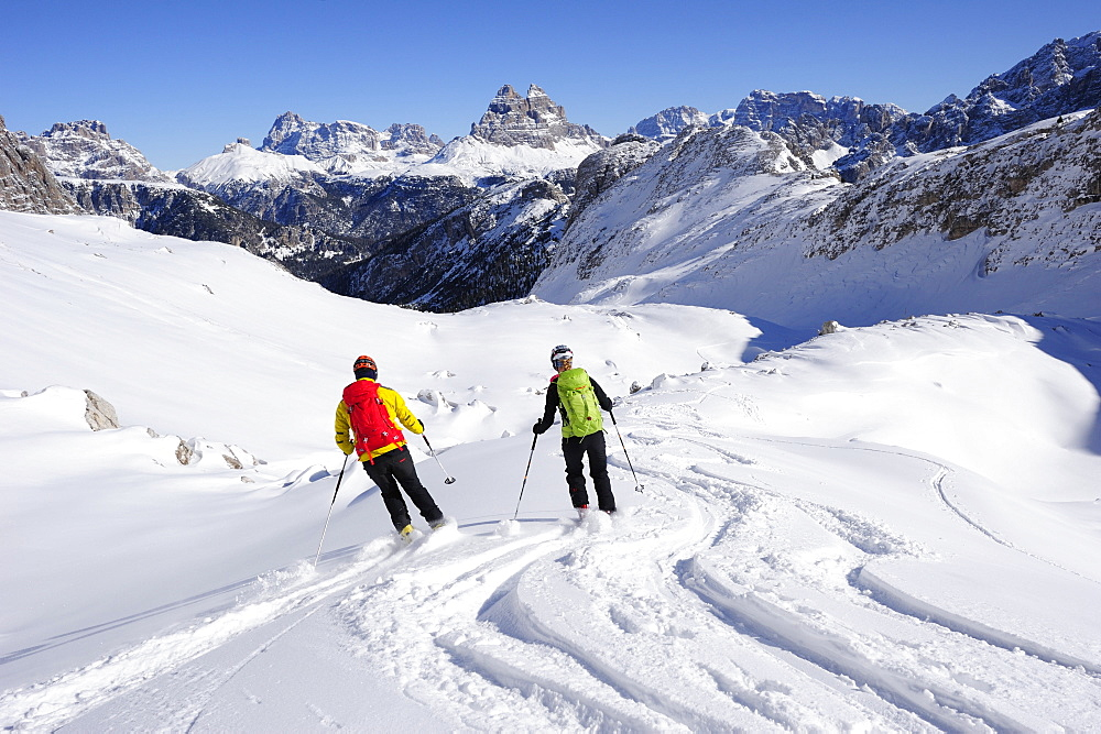 Young woman and young man descending with crosscountry skis from Corno d'Angolo, Tre Cime di Lavaredo in background, Corno d'Angolo, Cortina, Veneto, Dolomites, Italy, Europe